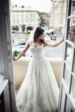 Herrliche Brunettebraut im sexy Hochzeitskleid, das auf Balkon aufwirft Stockfoto