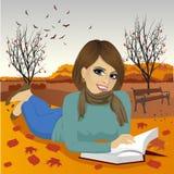 Herrliche Brunettefrau, die ein Buch im Herbstpark liest lizenzfreie abbildung