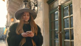 Herrliche Brunettefrau in einem grauen Hut, der in der gedrängten Stadtstraße steht und ihr Telefon für simsende Mitteilung verwe stock footage