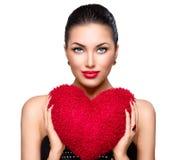 Herrliche Brunettefrau mit Herzen formte rotes Kissen Stockfotos
