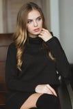 Herrliche durchdachte Frau im schwarzen Kleid, das auf ledernem Sofa sitzt Stockfotos