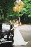 Herrliche elegante Braut, die nahe Luxushochzeit des stilvollen Retro- schwarzen Autos in der Weinleseart aufwirft Porträt stockfotos