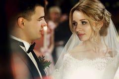 Herrliche emotionale blonde Braut, die hübschen Jungebräutigam betrachtet Stockfotos