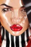 Herrliche erwachsene Frau mit nassem Gesicht und Streifen auf Hals und Haar Stockfotografie
