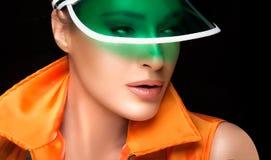 Herrliche Frau in der grünen Sonnenblende und in der bunten Sportkleidung lizenzfreie stockfotos