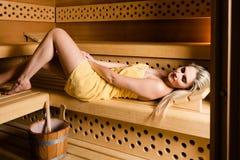 Herrliche Frau, die in der Sauna sich entspannt Stockfoto