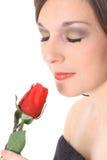 Herrliche Frau, die eine Rose riecht Stockbilder