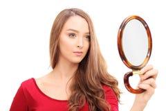 Herrliche Frau, die in einem Spiegel sich schaut Stockfotografie