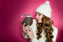 Herrliche Frau, die einen netten Spielzeugvogel mit Sankt-Hut hält Stockfotos