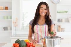 Herrliche Frau, die Gemüse während standingg vorbereitet lizenzfreie stockbilder