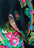 Herrliche Frau, die Gesicht durch Schal bedecken lässt Lizenzfreie Stockfotos
