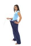 Herrliche Frau, die weg ihren Gewichtverlust im Baumwollstoff zeigt Stockbild