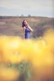 Herrliche Frau im blauen Kleid auf dem Blumengebiet am sonnigen Tag Stockbild