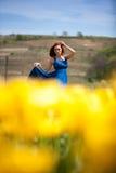 Herrliche Frau im blauen Kleid auf dem gelben Tulpengebiet Stockbild