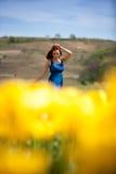 Herrliche Frau im blauen Kleid auf dem gelben Tulpengebiet Stockbilder