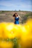 Herrliche Frau im blauen Kleid auf dem gelben Tulpengebiet Lizenzfreies Stockbild