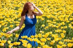 Herrliche Frau im blauen Kleid auf dem schönen Blumengebiet Lizenzfreies Stockbild