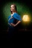Herrliche Frau im blauen Kleid im Weinleseraum Stockfoto