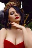 Herrliche Frau im roten Kleid mit Krone stockbilder
