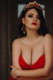 Herrliche Frau im roten Kleid mit Krone stockfotografie