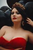 Herrliche Frau im roten Kleid mit Krone lizenzfreie stockfotografie