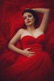 Herrliche Frau im roten Kleid mit Krone lizenzfreies stockfoto