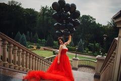 Herrliche Frau im roten Kleid mit schwarzen Ballonen lizenzfreie stockfotos