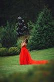 Herrliche Frau im roten Kleid mit schwarzen Ballonen stockfotografie