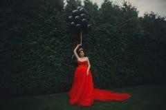 Herrliche Frau im roten Kleid mit schwarzen Ballonen stockfoto
