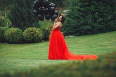 Herrliche Frau im roten Kleid mit schwarzen Ballonen lizenzfreie stockbilder
