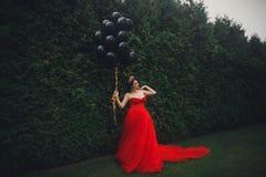 Herrliche Frau im roten Kleid mit schwarzen Ballonen stockfotos