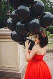 Herrliche Frau im roten Kleid mit schwarzen Ballonen stockbilder