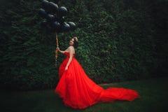 Herrliche Frau im roten Kleid mit schwarzen Ballonen stockbild