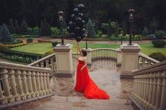 Herrliche Frau im roten Kleid mit schwarzen Ballonen lizenzfreies stockbild