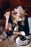 Herrliche Frau mit dem blonden Haar im eleganten Anzug und im Hut, sitzend im Café Lizenzfreies Stockbild