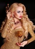 Herrliche Frau mit dem blonden Haar im luxuriösen Kleid, das Glas Champagner hält Lizenzfreie Stockfotografie