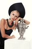 Herrliche Frau mit dem blonden Haar im russischen nationalen Hut mit Samowar Lizenzfreie Stockfotos