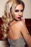 Herrliche Frau mit dem blonden Haar und hellem Make-up, tragendes luxuriöses Pailletten-Kleid Lizenzfreies Stockfoto