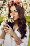 Herrliche Frau mit dem dunklen Haar, das im Frühjahr Garten aufwirft Lizenzfreie Stockbilder