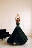 Herrliche Frau mit Make-up des dunklen Haares und des Abends im eleganten Kleid, das im Studio aufwirft lizenzfreies stockfoto