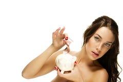 Herrliche Frau setzte etwas Geld in ihre piggy Querneigung ein Stockfotos