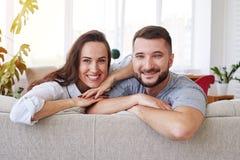 Herrliche Frau und Ehemann, welche die Freizeit sich entspannt auf Sofa verbringt Lizenzfreie Stockfotos