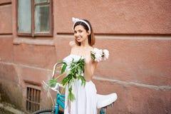Herrliche Frau, welche die Blumen aufwerfen nahe ihrem Fahrrad hält lizenzfreies stockfoto