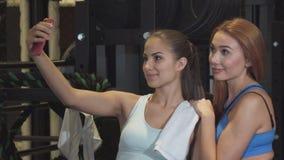 Herrliche Freundinnen, die zusammen selfies an der Turnhalle nachdem dem Trainieren nehmen stock video footage