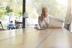 Herrliche Geschäftsfrau, die am Kopienraumholztisch mit offener Laptop-Computer arbeitet Stockfotos