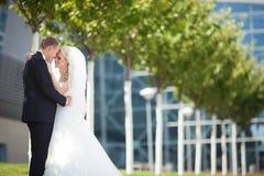 Herrliche glückliche blonde Braut und eleganter Bräutigam auf dem Hintergrund Lizenzfreie Stockfotografie