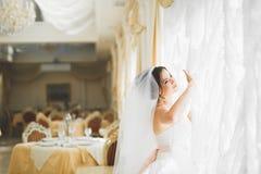 Herrliche glückliche Luxusbrunettebraut nahe einem Fenster auf dem Hintergrund des Weinleseraumes stockfotos