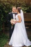 Herrliche Hochzeitspaare, die auf den Hinterhof des Paarhauses gehen Grüner Hintergrund stockfotos