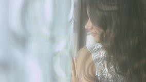 Herrliche junge aufwerfende Frau bei der Stellung am Fenster in einem Hotelzimmer stock video