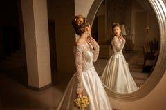 Herrliche junge blonde Braut, die den Spiegel betrachtet Stockfotos